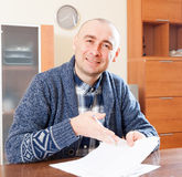 Man with documents. Man sitting with documents in home interior stock image