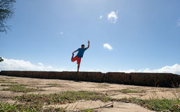 Man does Dancer Pose on Rock Wall Royalty Free Stock Photo