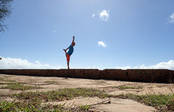 Man does Dancer Pose on Rock Wall Stock Image