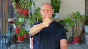 A man does exercises with his eyes looking at his finger and moving it away. The average plan stock video footage