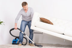 Man does house work with vacuum cleaner. Royalty Free Stock Images