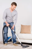 Man does house work with vacuum cleaner. Stock Photography