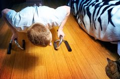 The man does push-ups at home room, and cat watch at him, Healthy lifestyle stock photo