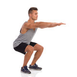 Man Does Squat. Muscular man showing a squat exercise, side view. Full length studio shot isolated on white Stock Images