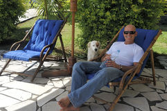 Man with dog. Man relaxing with his dog and a bottle of water Stock Images