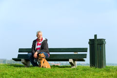 Man with dog. Elderly man with his dog at bench outdoor Stock Image