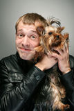 Man with dog. Young man holding dog yorkshire terrier with irony face Stock Photography