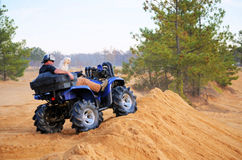 Man and Dog on ATV, Best Friends. Man sitting on top of dirt hill on his ATV with his best friend, a Havanese dog, as dust from the sandy track fills the royalty free stock images