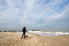 Man with dog at beach Stock Photos