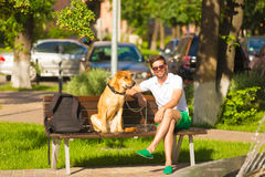 Man with dog on bench in park. Royalty Free Stock Photo