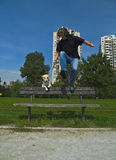 Man And Dog Are Best Friends Indeed. Adult man jumping over the bench  together with his dog pet at the promenade Stock Photo