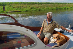 Man and dog in boat Stock Images