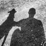 Man and dog cast shadows. Silhouettes of a man and his dog showing strong bond Royalty Free Stock Images
