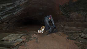 A man and a dog in a cave. Royalty Free Stock Photography