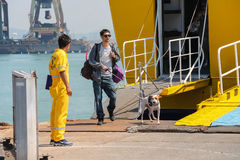 Man with dog coming out of ferry boat in seaport Stock Images