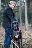 Man with dog in forest. Man with great dane dog in forest posing stock photo
