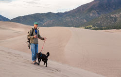Man with dog on Great Sand Dunes NP Royalty Free Stock Image