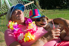 Man with dog in hammock Stock Images
