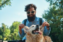 Man and dog having fun, playing, making funny faces while restin. G in the park. Life is beautiful, best friends concept royalty free stock images