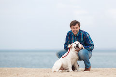 Man and dog having fun on seaside. royalty free stock image
