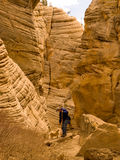 Man and dog hiking in narrow desert canyon Stock Photo