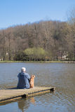 Man with dog on landing stage Stock Images