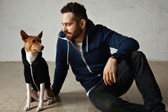 Man and dog in matching hoodies. An attractive young man and his bassenji dog wearing matching hoodies sit on the floor next to white wall stock images