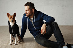 Man and dog in matching hoodies. A cute basenji dog and its owner wearing matching outfits sitting on the floor Stock Photo