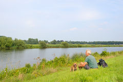 Man with dog near the river Royalty Free Stock Image