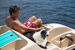 Man and dog in paddle boat Royalty Free Stock Images