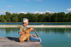 Man with dog on pier Stock Images
