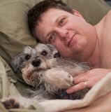 Man and dog relaxing. Caucasian man relaxing in bed with his friendly miniature schnauzer dog Stock Photo