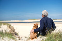 Man with dog on sand dune royalty free stock photography