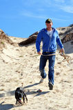 Man and dog in sand dunes Stock Photography