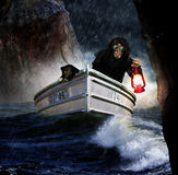Man and dog searching. A cloaked man in a boat with his dog holding a lantern as they search for something in a stormy rain soaded sea between cliffs Royalty Free Stock Images