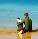 Man and dog siting in the water Royalty Free Stock Image