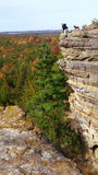 Man with dog sits atop cliff overlooking fall foliage Royalty Free Stock Image