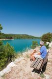 Man with dog sitting in French landscape. Man sitting at lake de Sainte Croix in the French Provence royalty free stock photo