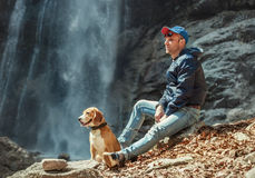 Man with dog sitting near waterfall Stock Images