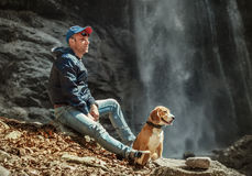 Man with dog sitting near waterfall Stock Photography