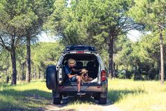 Man with dog sitting in off road car boot. In forest. Freedom and traveling couple stock photos