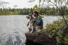 Man and dog are sitting on the stone near of lake and looking into the distance Royalty Free Stock Photo