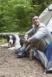 Man With Dog Sitting By Tent Stock Photography