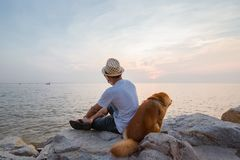 Man and a dog sitting together on the stone near the sea stock photo