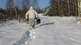 Man and dog in snow stock video footage