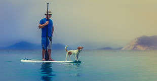 Man and Dog Standing on White Surf Board in Water Painting Stock Photos