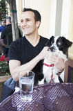 Man and dog at a street cafe. Caucasian man sitting at a street cafe table with his pet dog on his lap Stock Images