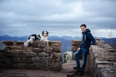 Man and dog travel . Pet and his friend in nature. Australian Shepherd and its owner stock photo