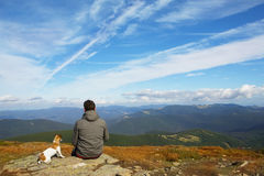 Man and dog traveling in nature. Man and his faithful friend the dog admire the mountain scenery in the campaign royalty free stock photos