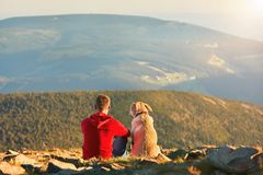 Man with dog on the trip in the mountains. Young tourist and his dog are resting and together watching the sunset Stock Photo